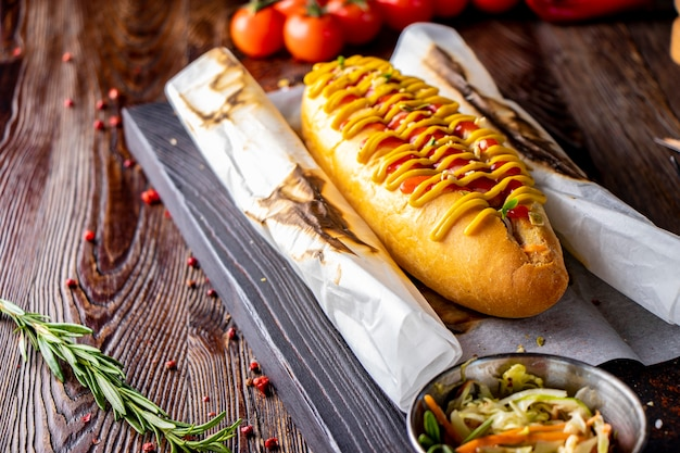 Hot-dog avec saucisse est situé sur une planche de bois contre une surface sombre, style rustique, orientation horizontale, espace de copie