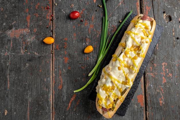 Hot dog avec saucisse, fromage et maïs. concept de restauration rapide et de mauvaise alimentation. bannière, menu, lieu de recette pour le texte, vue de dessus