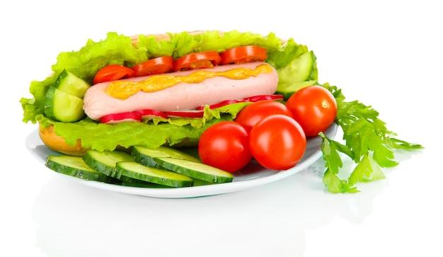Hot-dog savoureux avec des légumes isolés sur blanc