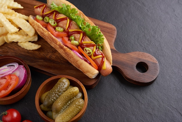 Hot dog tout bœuf grillé gastronomique avec accompagnements et frites. des hot dogs délicieux et simples avec de la moutarde, du poivre, de l'oignon et des nachos. hot-dogs entièrement chargés de garnitures assorties sur une planche à pagaie.