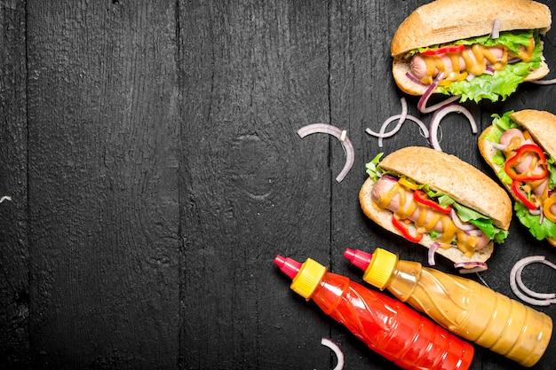 Hot-dogs aux oignons, tomates et moutarde chaude sur tableau noir.