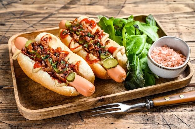 Hot-dogs avec bacon frit, oignon et concombres marinés.