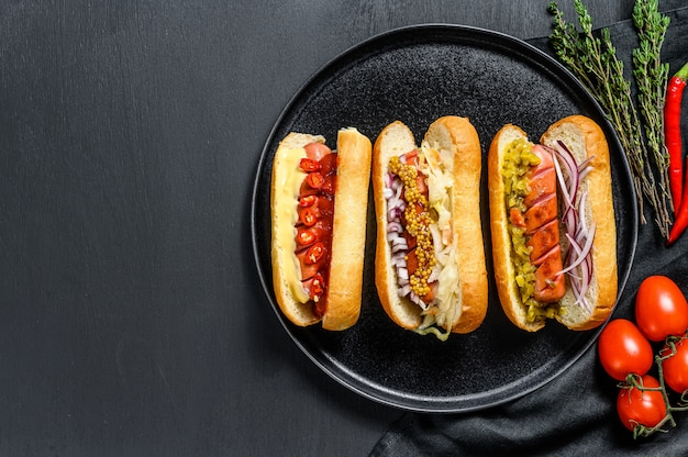 Hot-dogs entièrement chargés de garnitures assorties sur un plateau. délicieux hot-dogs avec des saucisses de porc et de boeuf. fond noir. vue de dessus. espace copie