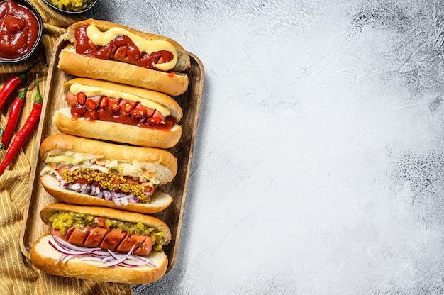 Hot-dogs entièrement chargés de garnitures assorties sur un plateau