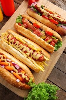 Hot-dogs frais sur planche à découper et bouteilles sur fond de bois