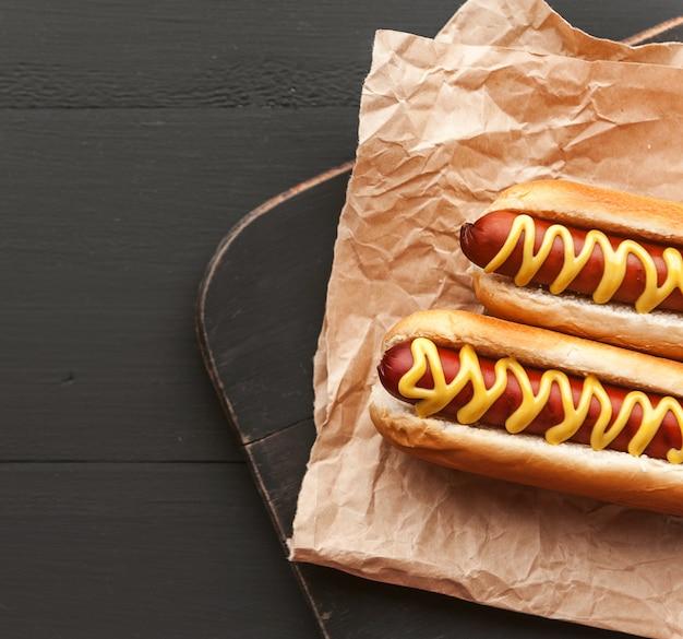 Hot-dogs grillés au barbecue avec de la moutarde américaine jaune, sur un fond en bois foncé