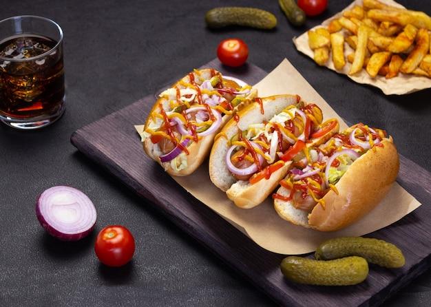 Hot-dogs avec légumes, moutarde et ketchup sur une planche à découper, vue latérale restauration rapide, cuisine de rue