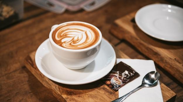 Hot latte art dans une tasse blanche servie avec du sucre sur une assiette en bois avec une cuillère et une serviette en argent.