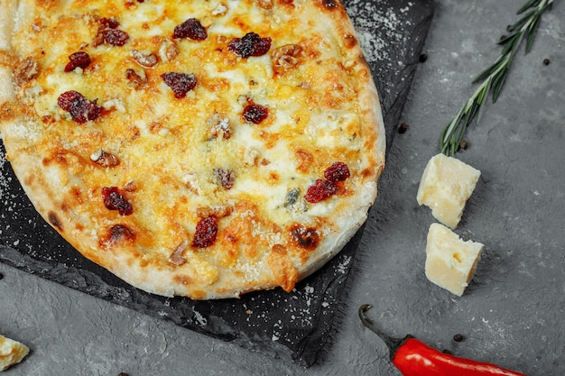 Hot quatre fromages délicieuse pizza américaine maison rustique avec une croûte épaisse sur table noire.