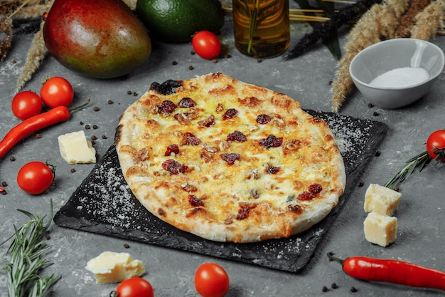 Hot quatre fromages délicieuse pizza américaine maison rustique avec une croûte épaisse sur table noire