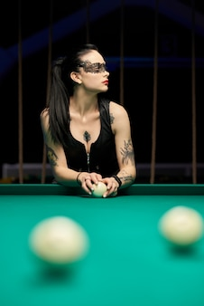 Hot sexy jeune femme jouant au billard. femme au tatouage, brune sexy.
