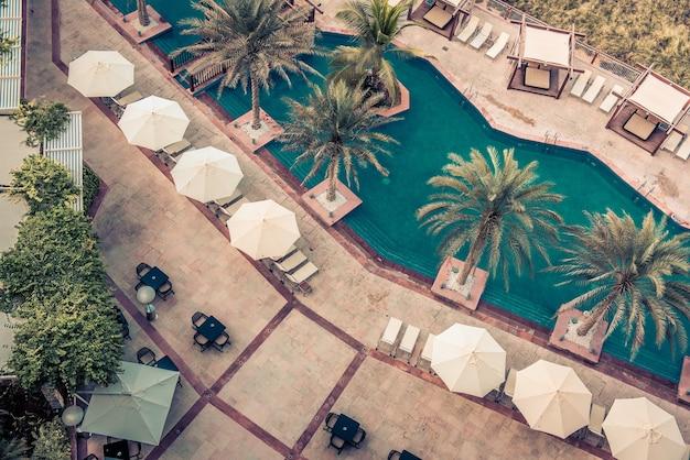 Hôtel au bord de la piscine avec parasols et palmiers. vue de dessus