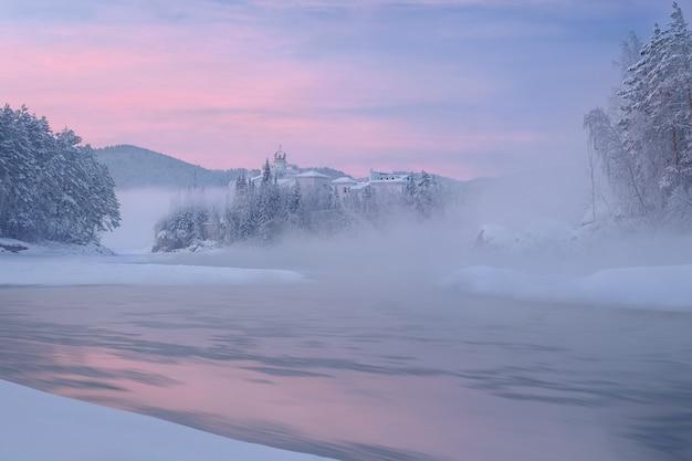 Hôtel, qui se dresse sur la rive d'une rivière gelée, à moitié caché dans la brume de la rivière