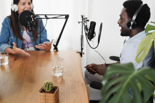 Des hôtes multiraciaux diffusent des podcasts ensemble dans un home studio - focus sur les écouteurs de l'homme africain