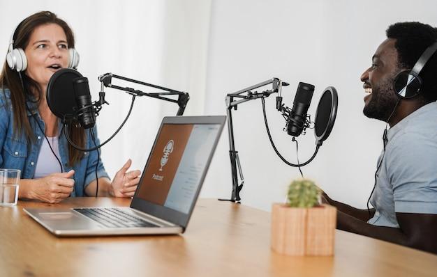 Des hôtes multiraciaux diffusent des podcasts ensemble dans un home studio - focus sur le visage de l'homme africain
