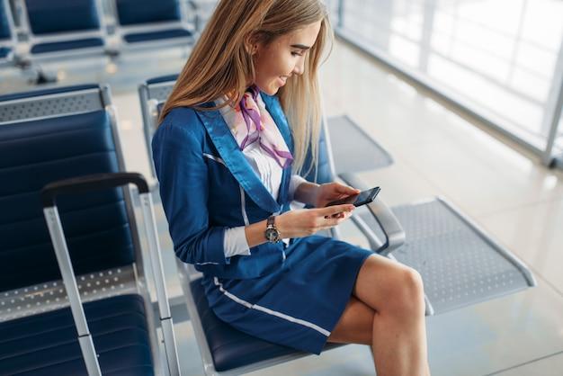 Hôtesse de l'air à l'aide de téléphone dans la zone d'attente de l'aéroport