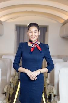 Hôtesse de l'air asiatique posant avec le sourire au milieu de l'allée à l'intérieur du siège passager de l'avion sur l'arrière-plan