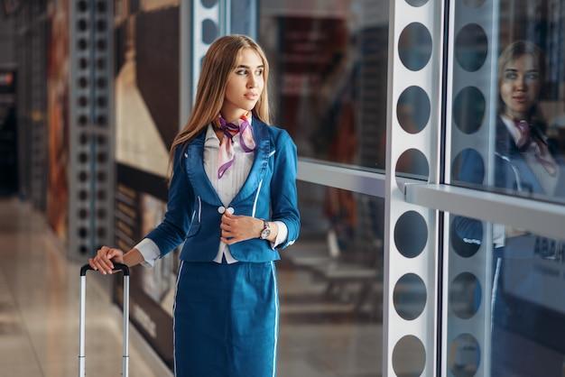 Hôtesse de l'air avec bagages à main et café à l'aéroport