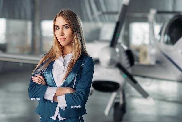 Hôtesse de l'air contre avion à hélice dans le hangar