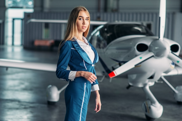 Hôtesse de l'air contre avion turbopropulseur dans le hangar
