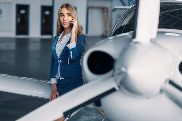 Hôtesse de l'air contre le moteur à hélice de l'avion