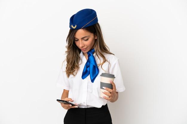 Hôtesse de l'air sur fond blanc isolé tenant du café à emporter et un mobile