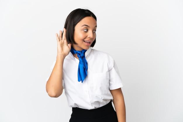Hôtesse de l'air sur fond isolé écoutant quelque chose en mettant la main sur l'oreille