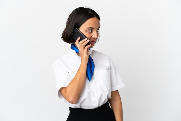Hôtesse de l'air sur fond isolé en gardant une conversation avec le téléphone portable avec quelqu'un