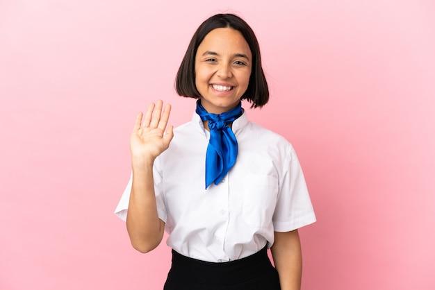 Hôtesse de l'air sur fond isolé saluant avec la main avec une expression heureuse