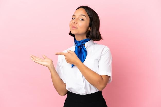 Hôtesse de l'air sur fond isolé tenant un espace de copie imaginaire sur la paume pour insérer une annonce