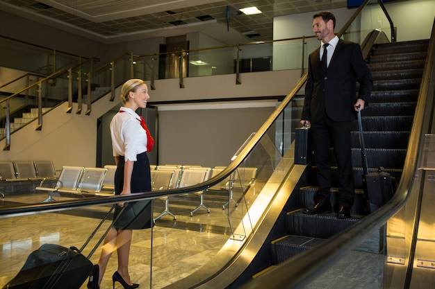 Hôtesse de l'air interagissant avec l'homme d'affaires