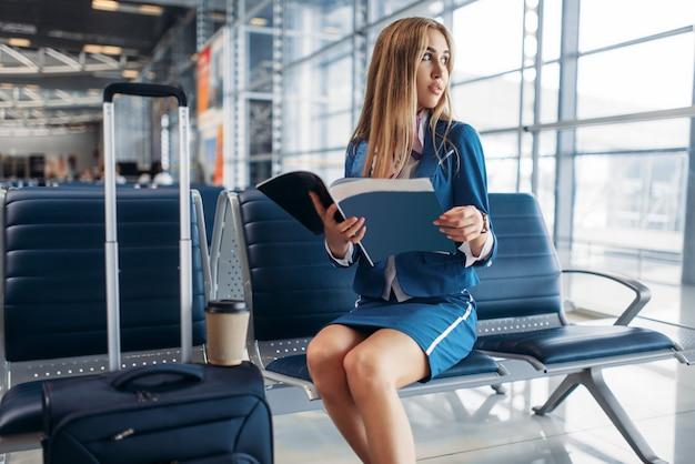 Hôtesse de l'air lit le magazine dans la zone d'attente de l'aéroport
