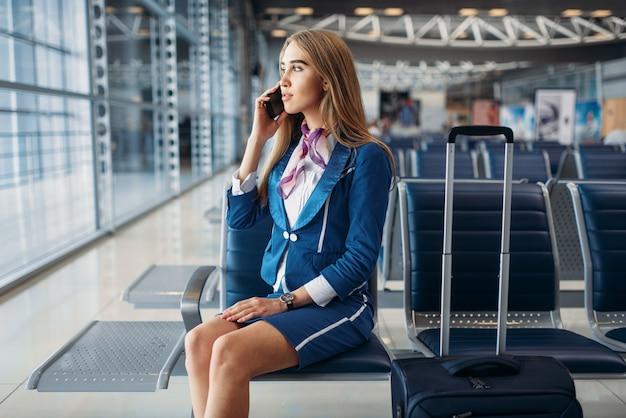 Hôtesse de l'air parlant par téléphone mobile à l'aéroport