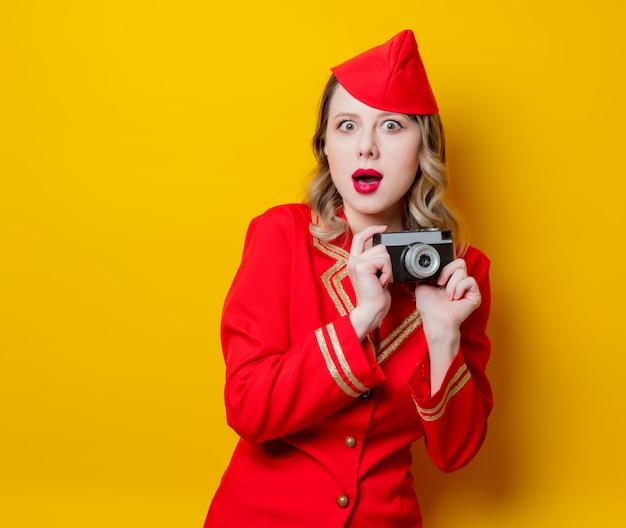 Hôtesse de l'air portant un uniforme rouge avec appareil photo