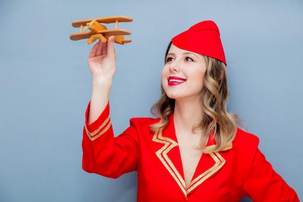 Hôtesse de l'air portant un uniforme rouge avec avion en bois