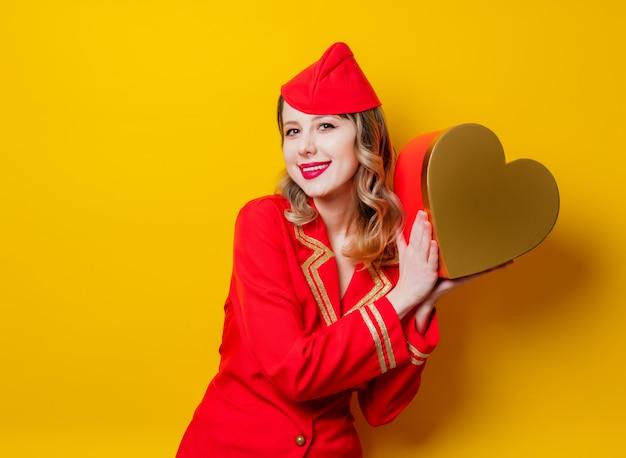 Hôtesse de l'air portant un uniforme rouge avec boîte de gfit de vacances en forme de coeur
