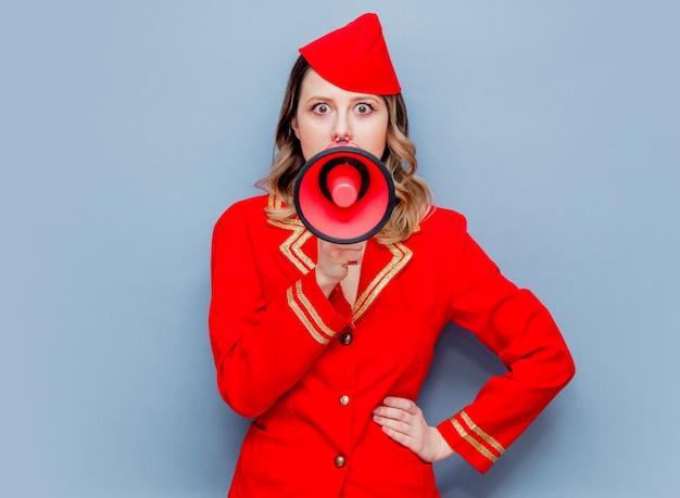 Hôtesse de l'air portant un uniforme rouge avec mégaphone