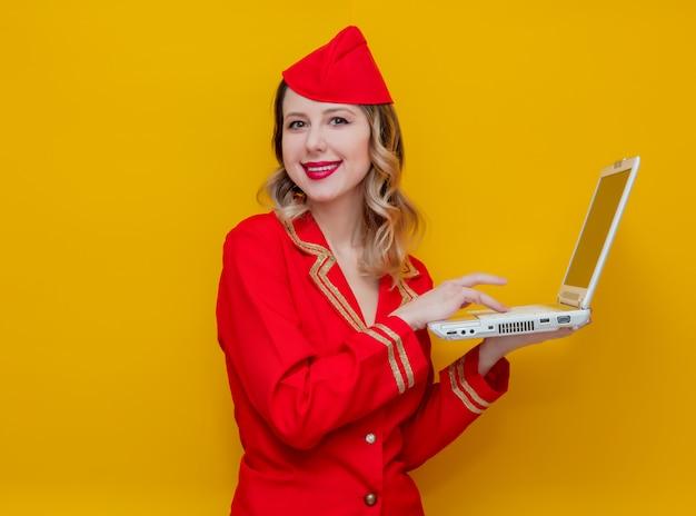 Hôtesse de l'air portant un uniforme rouge avec ordinateur portable