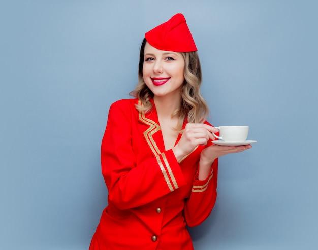 Hôtesse de l'air portant un uniforme rouge avec une tasse de café ou te