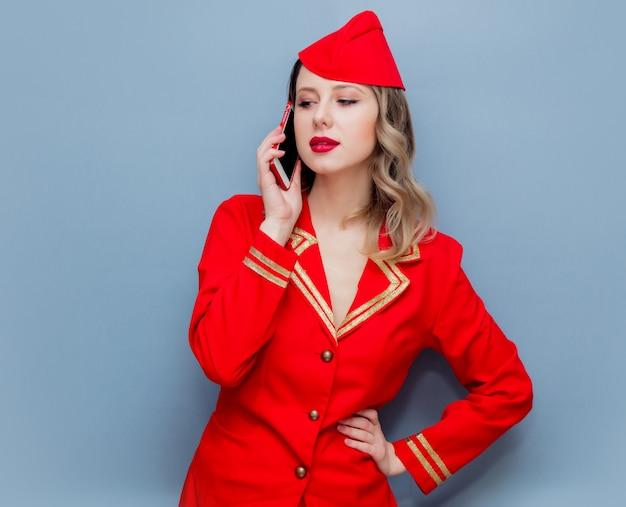 Hôtesse de l'air portant un uniforme rouge avec téléphone portable