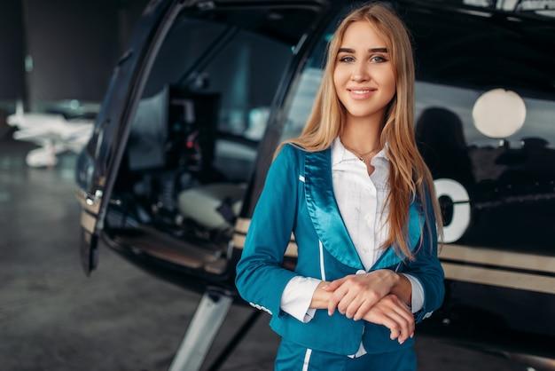 Hôtesse de l'air pose contre l'hélicoptère dans le hangar