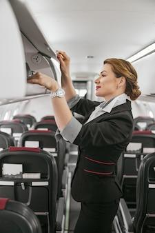 L'hôtesse de l'air prend les bagages de l'étagère dans la cabine passagers du jet d'avion. intérieur d'avion moderne. une femme européenne souriante porte un uniforme. aviation civile commerciale. concept de voyage aérien