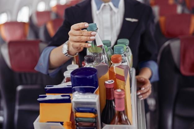 L'hôtesse de l'air prend la bouteille d'eau du chariot dans la cabine passagers du jet d'avion. intérieur d'avion moderne. image recadrée d'une femme en uniforme. aviation civile commerciale. concept de voyage aérien