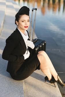 Une hôtesse de l'air en uniforme est assise sur les marches à côté de la valise