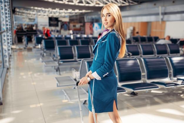 Hôtesse de l'air avec valise dans la salle d'attente de l'aéroport