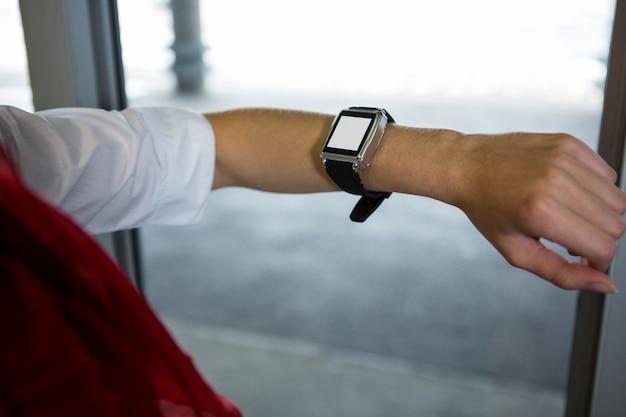 Hôtesse de l'air vérifiant l'heure sur sa smartwatch