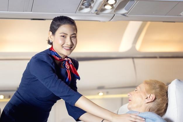 Une hôtesse de l'air vêtu d'un passager âgé dormant dans le siège passager