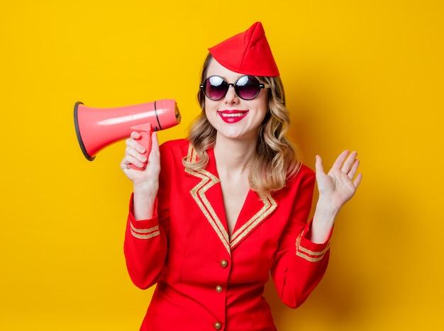 Hôtesse de l'air vintage vêtu de l'uniforme rouge avec mégaphone