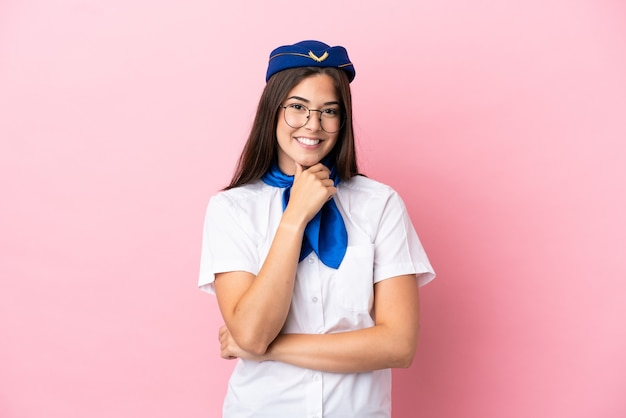 Hôtesse d'avion femme brésilienne isolée sur fond rose avec des lunettes et souriant