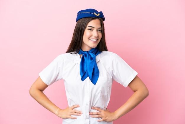 Hôtesse d'avion femme brésilienne isolée sur fond rose posant avec les bras à la hanche et souriant
